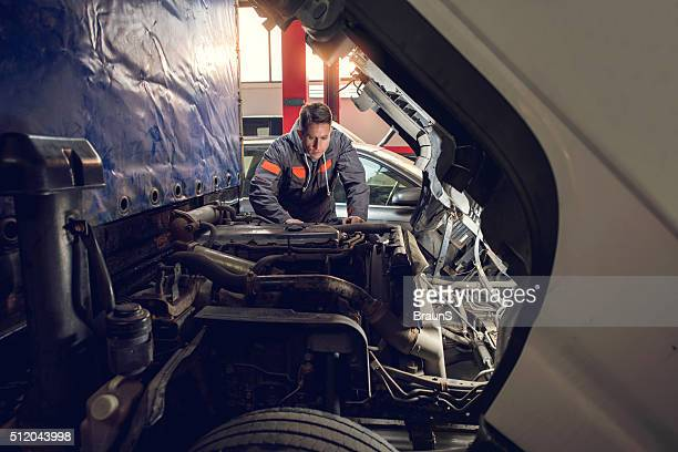 Mid adult mechanic repairing a truck in auto repair shop.