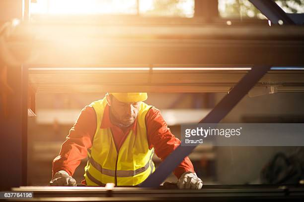 Mid adult metal worker working in industrial building.
