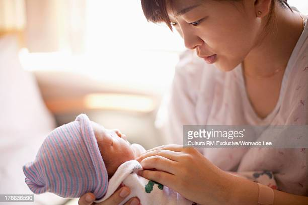 Mid adult mother holding newborn baby girl