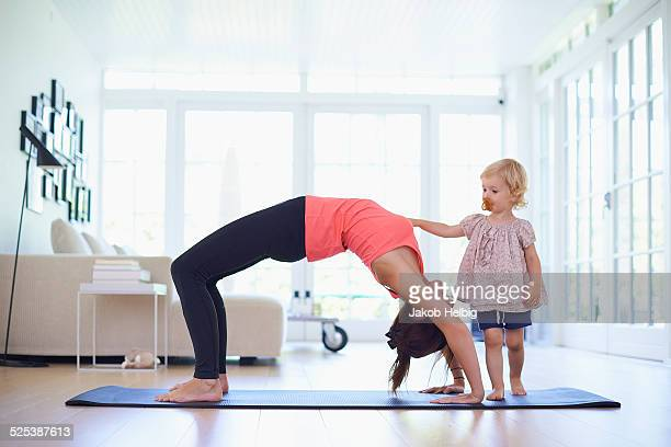 Mid adult mother practicing yoga with curious toddler daughter