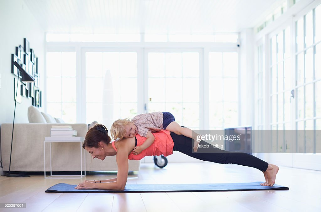 Mid adult mother practicing yoga with toddler daughter on top of her : Foto de stock
