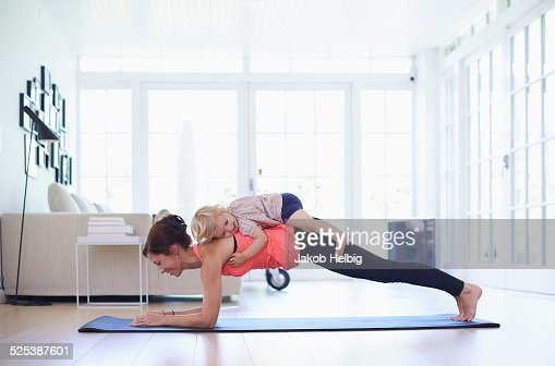 Mid adult mother practicing yoga with toddler daughter on top of her
