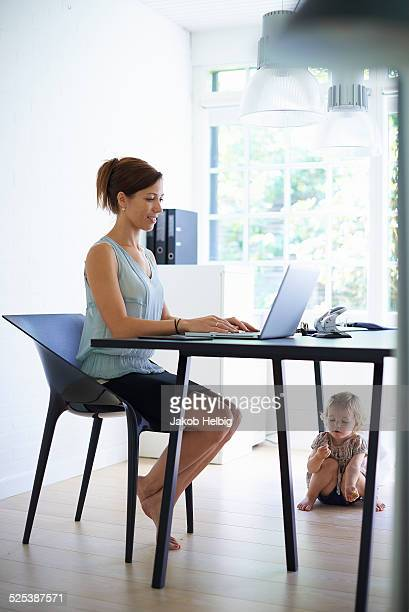 Mid adult mother typing on laptop with toddler daughter under the table
