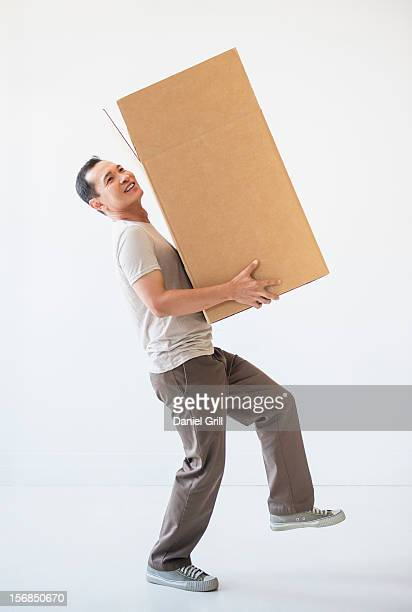 Mid adult moving cardboard heavy box