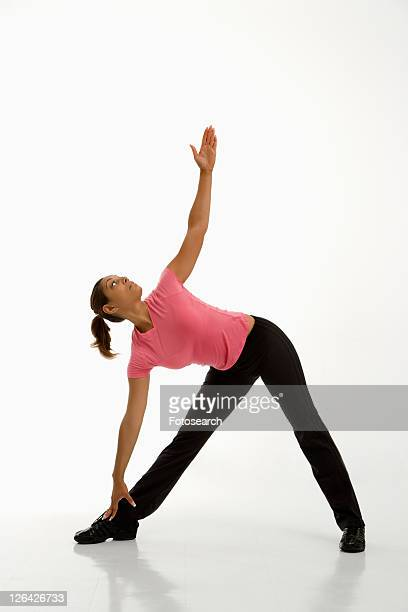 Mid adult multiethnic woman wearing exercise clothing holding yoga pose and stretching.