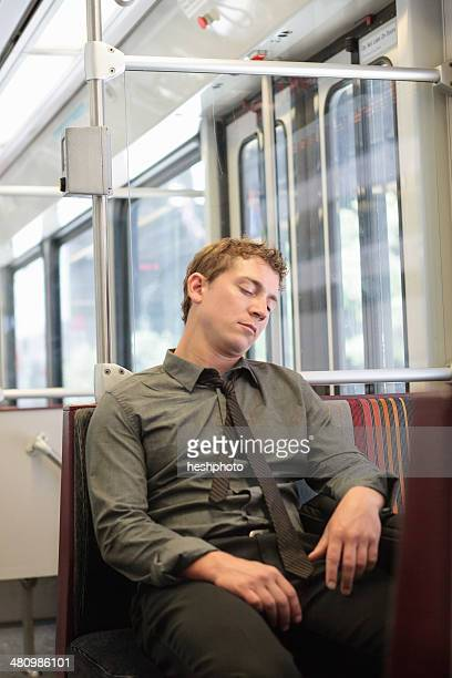 Mid adult office worker snoozing on train journey