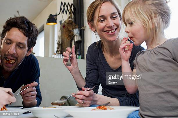 Mid adult parents and two daughters eating a spaghetti meal