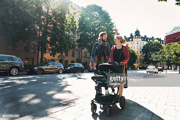 Mid adult parents with baby boy and stroller walking on sidewalk in city