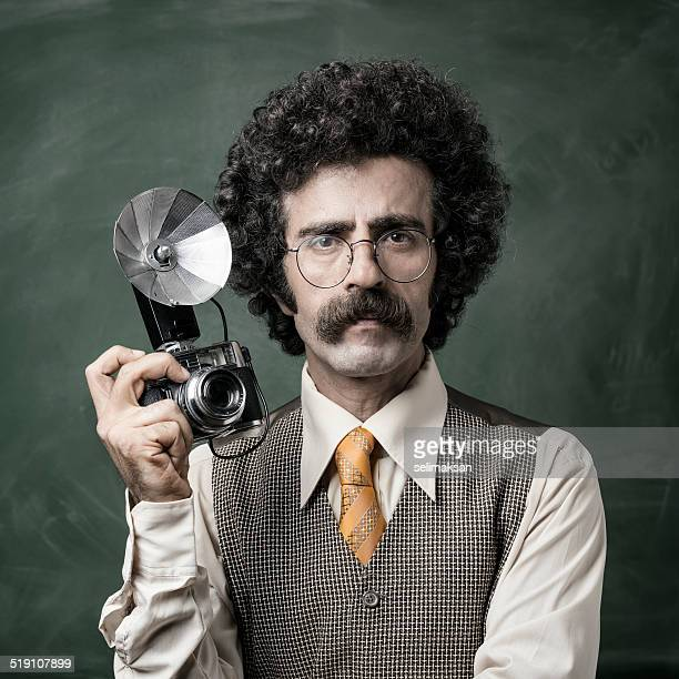 Mid adult photographer holding old fashioned camera
