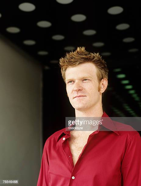 Mid adult redheaded man,looking away,upper half