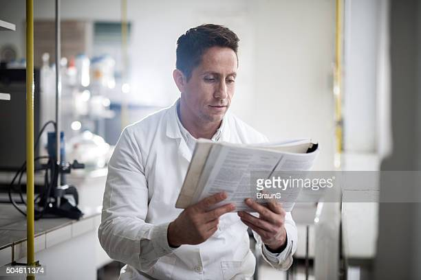 Mid adult scientist sitting in laboratory and reading medical book.