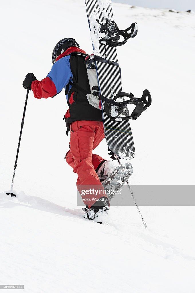 Mid adult snowboarder walking uphill, Obergurgl, Austria