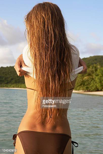 Mid adult taking t-shirt off in ocean (rear view)