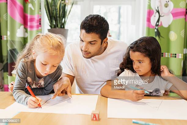 Mid adult teacher assisting female students in drawing at preschool