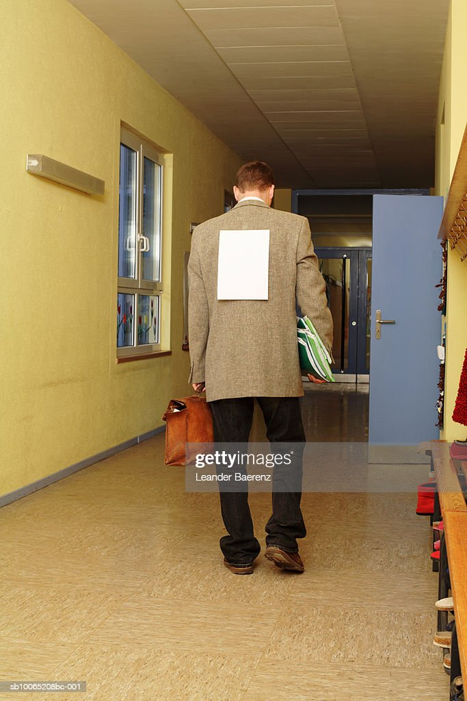Mid adult teacher walking corridor with sheet of paper on back : Stock Photo