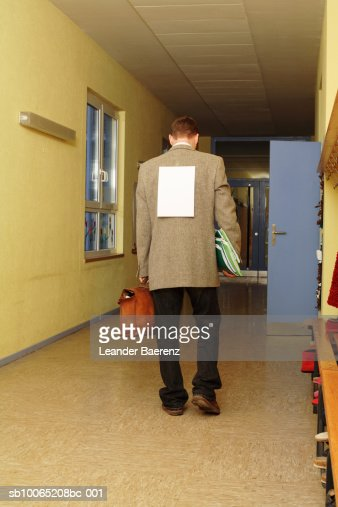 Mid adult teacher walking corridor with sheet of paper on back : ストックフォト