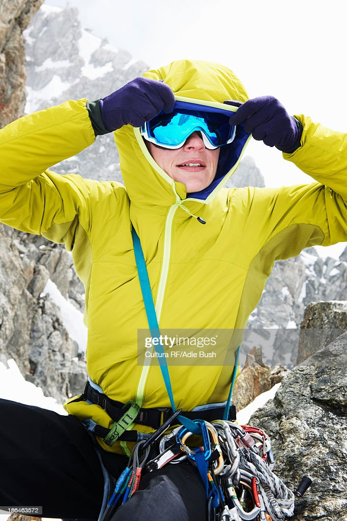 Mid adult woman adjusting ski goggles
