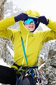 Mid adult woman adjusting ski goggles
