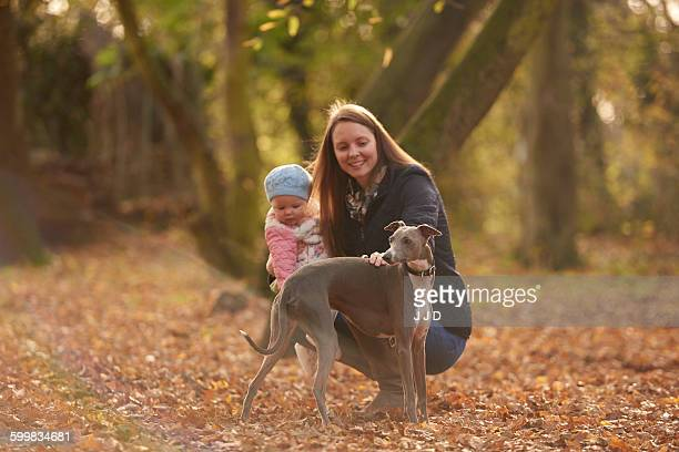 Mid adult woman and baby daughter petting dog in autumn park