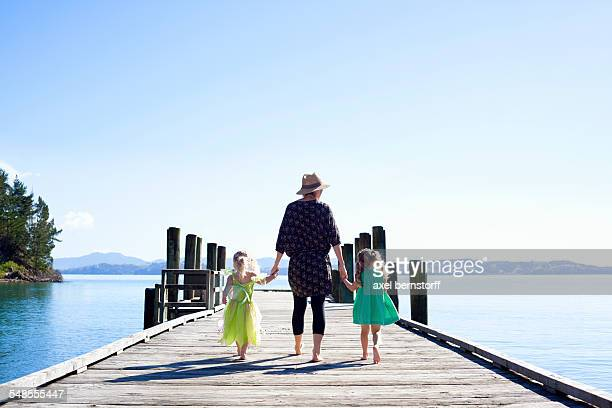 Mid adult woman and daughters strolling on pier, New Zealand