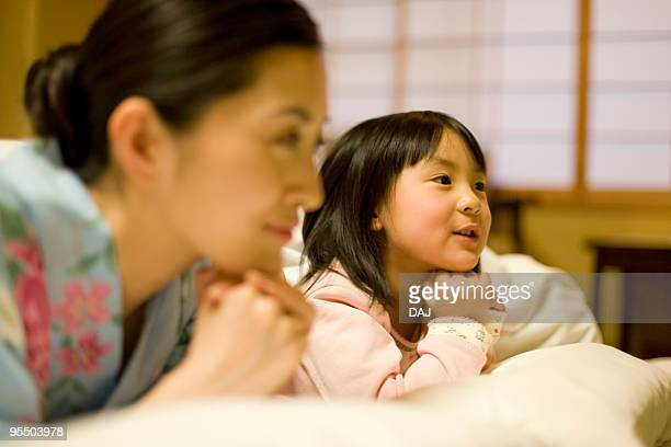 Mid adult woman and girl on Futon, smiling