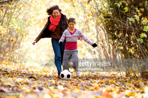 Mid adult woman and her daughter playing with a soccer ball : Stock Photo