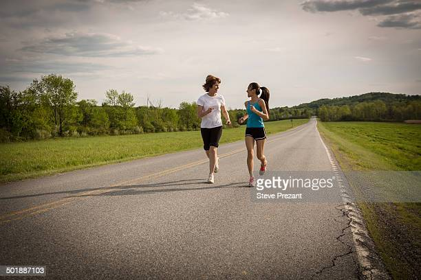 Mid adult woman and teenage girl running on road