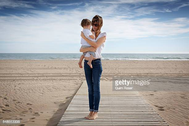 Mid adult woman and toddler daughter on beach, Castelldefels, Catalonia, Spain