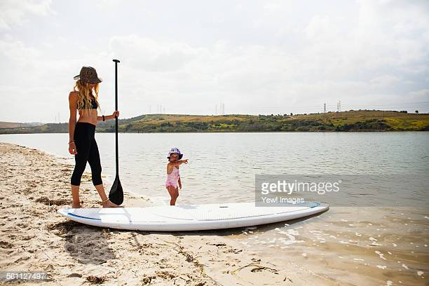 Mid adult woman and toddler daughter with paddleboard on beach, Carlsbad, California, USA