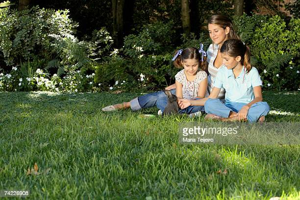 Mid adult woman and two girls (7-11) sitting on grass, playing with rabbit
