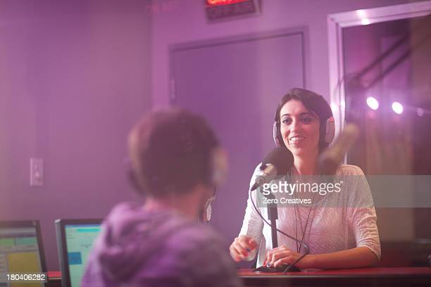 Mid adult woman and young man broadcasting in recording studio