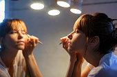 Mid adult woman applying eyeliner in bathroom mirror