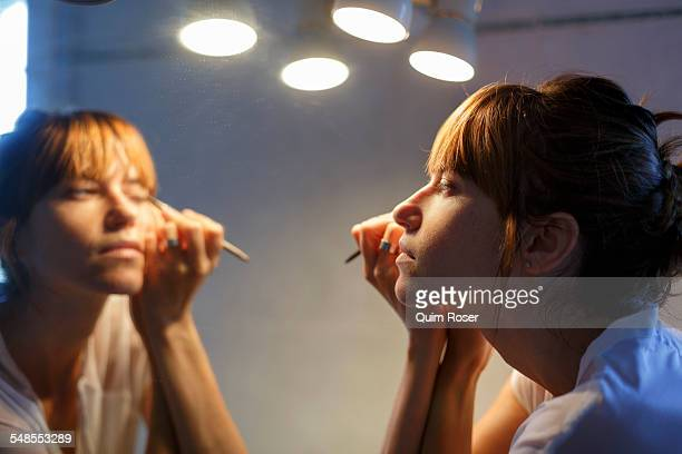 Mid adult woman applying eyeliner in bathroom mirror