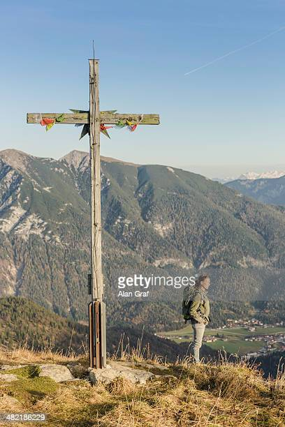 Mid adult woman backpacker and wooden cross, Achensee, Tyrol, Austria