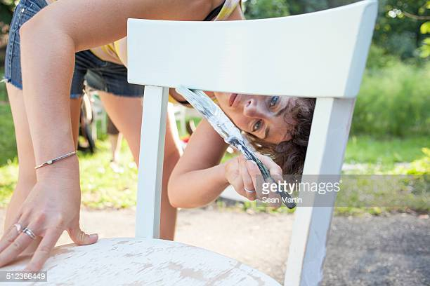 Mid adult woman bending forward to paint and restore chair in garden