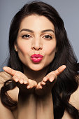Mid adult woman blowing a kiss