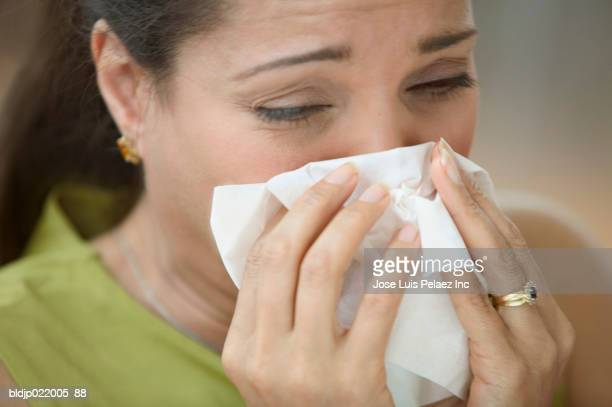 Mid adult woman blowing her nose