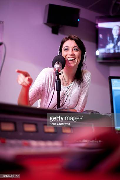 Mid adult woman broadcasting in recording studio