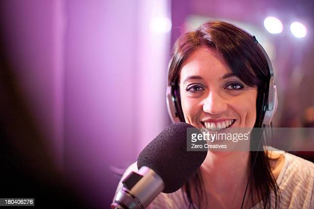 Mid adult woman broadcasting in recording studio, portrait
