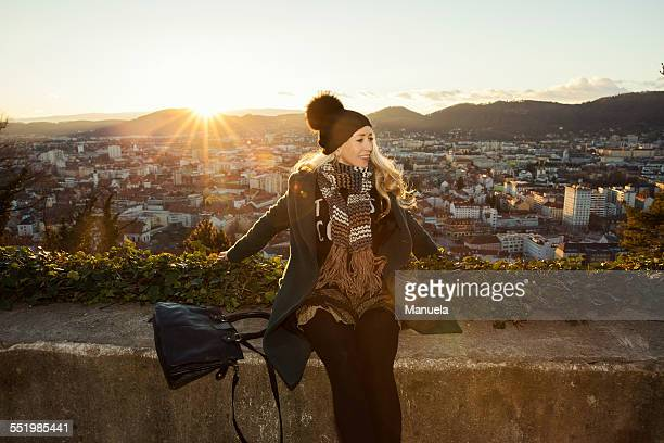 Mid adult woman by wall overlooking Graz, Styria, Austria