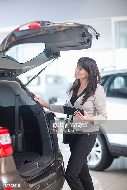 Mid adult woman checking car boot in showroom
