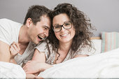 Mid adult woman couple fooling around on bed