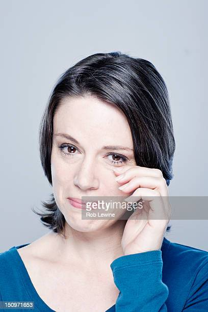 Mid adult woman crying, studio shot