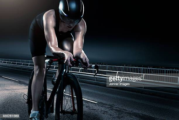 Mid adult woman cycling at night
