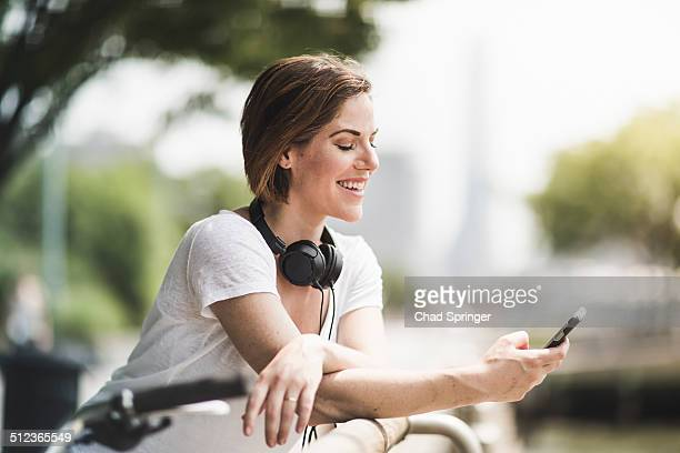 Mid adult woman cyclist looking at texts on her smartphone