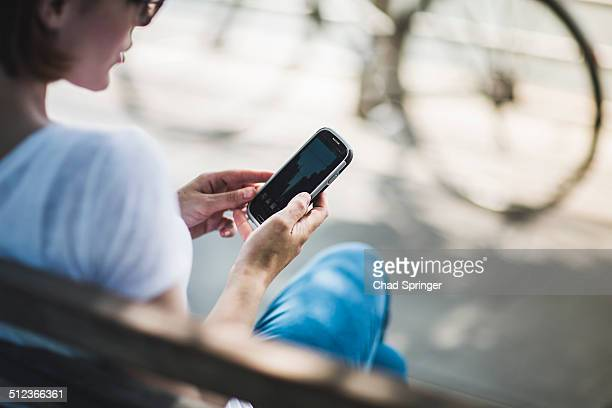 Mid adult woman cyclist sitting on bench looking at smartphone