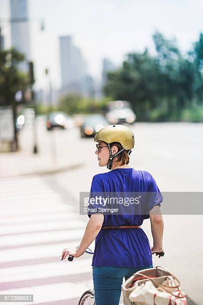 Mid adult woman cyclist waiting at pedestrian crossing, New York City, USA