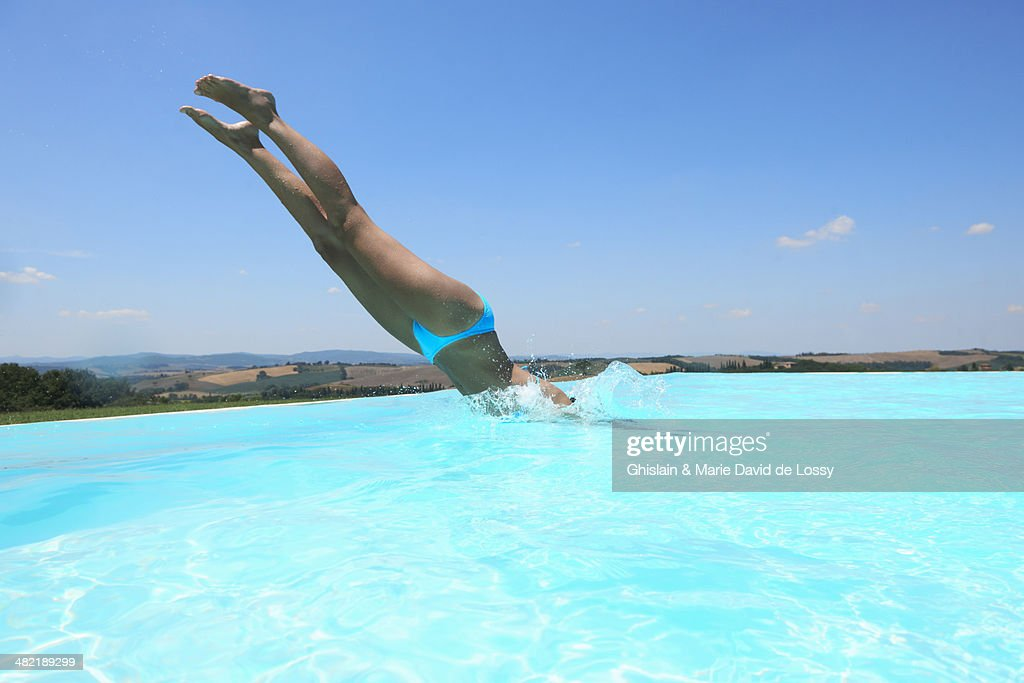 Mid Adult Woman Diving Into Swimming Pool Stock Photo