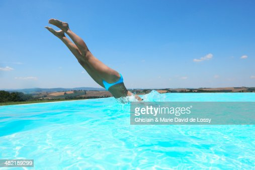 Mid Adult Woman Diving Into Swimming Pool Stock Photo ...