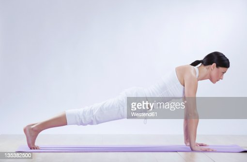 Mid adult woman doing chaturanga dandasana against white background